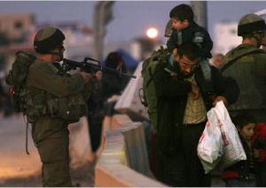 idf guard points gun at palestinian